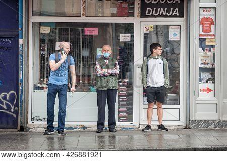 Belgrade, Serbia - June 6, 2021: Unhappy Old Senior Man Wearing A Respiratory Facemask  Next To Youn