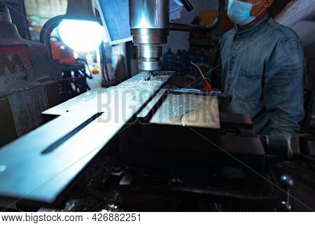 A Man Wear Surgical Mask Working With Milling Machine. Tool For Cut Metal Workpiece. Vertical Millin
