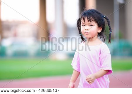 Portrait Of Cute Asian Girl Looks At The Camera While Jogging At The Stadium. Child Smiled Slightly.