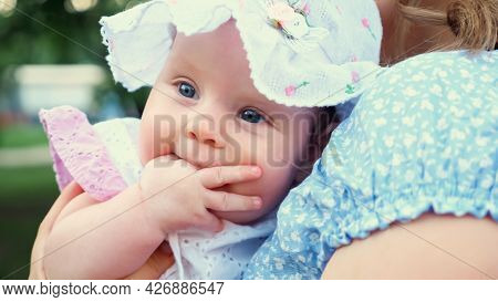 Cute Baby Girl With Blue Eyes In Panama Looks Around And Sucks Finger Sitting In Blonde Mother Arms