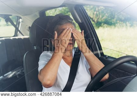 Mature Woman Driver Sitting At The Wheel In A Car, Frightened Of A Road Accident And Covering Her Ey