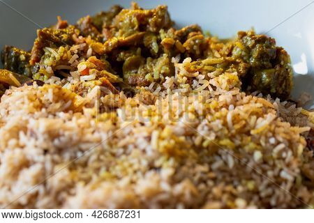 Close Up Of Jamaican Curried Goat Served With Rice And Peas