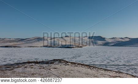 The Frozen Siberian Lake Among Deserted Shores. On Ice And Hills Lies Snow. Clear Blue Sky. Sunny Wi
