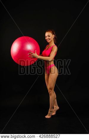 Fit Young Woman Exercising With Fitness Ball Over Dark Background