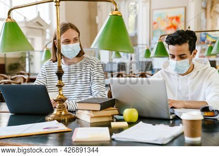 Young multiracial student man in face mask doing homework at library