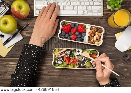 First Person Top View Photo Of Female Hands Eating Healthy Food From Two Lunchboxes And Typing On Ke