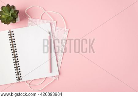 Top View Photo Of Two Pink Medical Facemasks Open Workbook Pen And Flowerpot On Isolated Pastel Pink