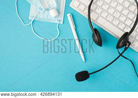 Top View Photo Of Black Headset With Microphone Pen White Keyboard Two Medical Facemasks And Sanitiz