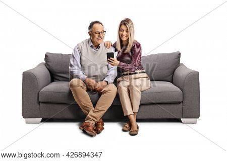 Elderly man and a young woman sitting on a sofa and looking at a mobile phone isolated on white background