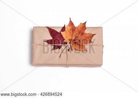 Gift In Craft Paper With Autumn Leaves On A White Background, Package, Delivery, Autumn Mood, Surpri