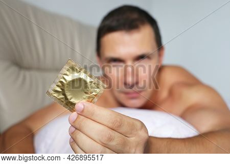 Muscular Man Lying With Condom In Bed. Concept Of Safety Sex, Contraception