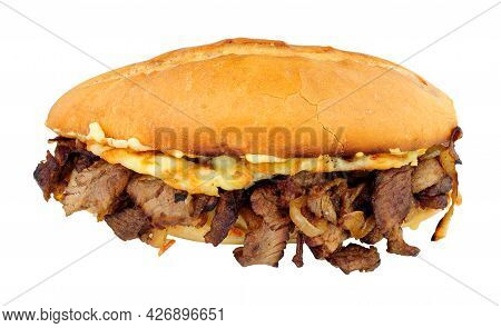 Steak And Cheese Sandwich With Fried Onions In A Crusty Bread Roll Isolated On A White Background