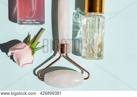 Massage Roller For The Face Made Of Rose Quartz With Bottles Of Cosmetic Oil Or Serum On A Blue Back