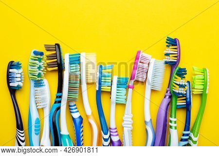 Toothbrushes On A Yellow Background. Concept Toothbrush Selection. Oral Cavity Care. Dental Hygiene.