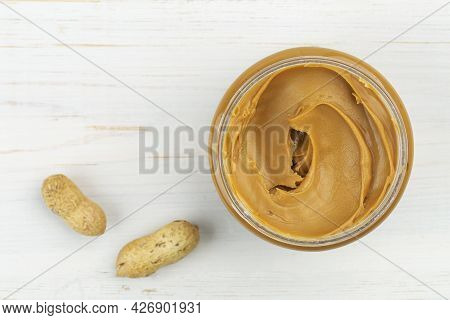 Jar Of Peanut Butter On A White Wooden Table With Peanuts Scattered Nearby. Space For Text. Top View