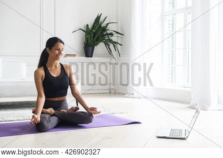 Young Beautiful Indian Woman Practicing Yoga With An Online Classes At Home, Athletic Mixed-race Fem