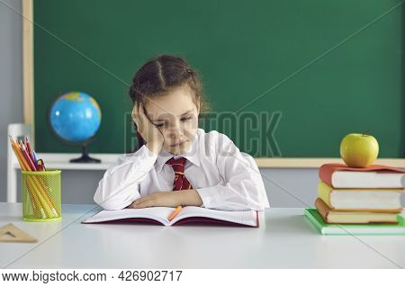 Sad Schoolgirl Looks At A Book While Sitting In Class. A Math Problem In A Child At School