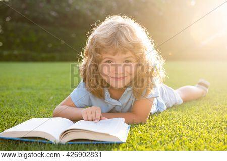 Kid Boy Reading Interest Book In The Garden. Summertime Fun. Cute Boy Lying On The Grass Reading A K