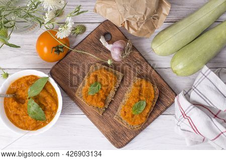 Dish With Squash Caviar Decorated With Basil On A White Wooden Background. Squash Spread, Zucchini C