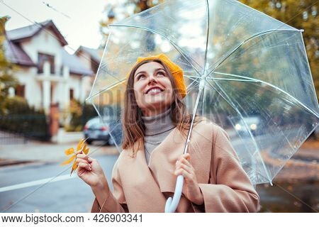 Happy Young Woman Walking Outdoors Under Transparent Umbrella During Rain Holding Yellow Leaves. Sty