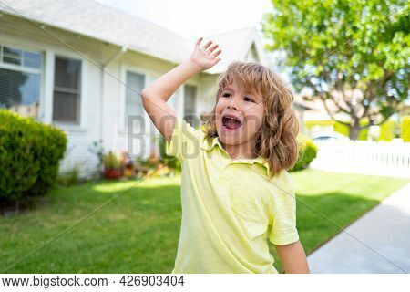 Boy With Good Bye Or Hello Sign Outdoor. Kids With Funny Face Bye Bye Hand On Backyard. Emotional Ch