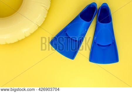 Blue Flippers, Swimming Circle On A Yellow Background. Flat Lay. Copy Space