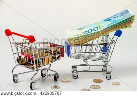 A Bundle Of 200 New Israeli Shekels On A Grocery Cart And A Pile Of Israeli Coins On A Grocery Cart