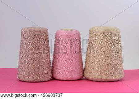 Pastel Color Bobbins Of Wool Yarn For Hand And Machine Knitting On A Pink Background
