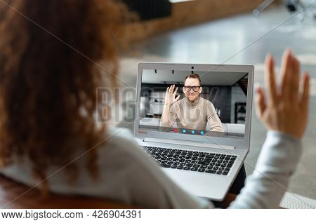 Young Woman With Curly Hairstyle Sitting At The Laptop, Chatting With Male Friend, Colleague, Talkin