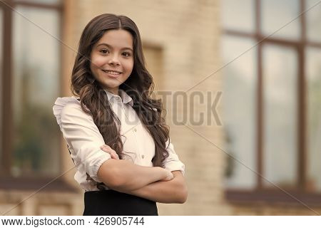 Little But Confident. Little Child Keep Arms Crossed Outdoors. Little Girl Wear School Uniform. Back
