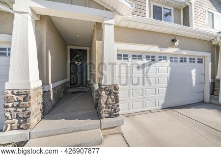 Front Exterior Of A House With White Sectional Garage Door With Window Panels