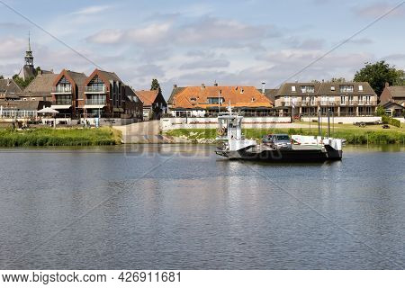 Broekhuizen, The Netherlands - June 19, 2021: Small Ferry Crossing River Meuse Near Dutch Village Br