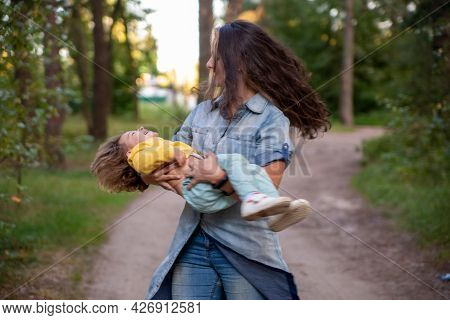 Young Mother Is Spinning With A Baby In Her Arms. Happy Mom Dancing With Toddler On The Background O