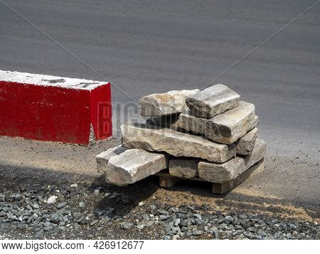 Old Used Curbs Are Stacked At The Edge Of An Asphalt Road Next To A Red-painted Boundary Stone. Road