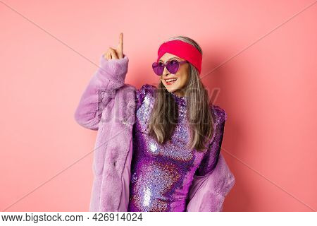 Asian Old Woman In Fashionable Glittering Dress And Purple Faux Fur Coat Dancing Disco, Pointing Fin