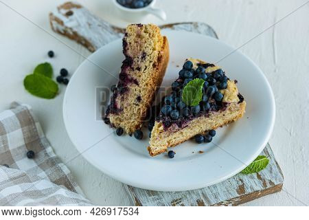 Sliced Blueberry Sponge Cake On A White Plate On A Light Concrete Background. Baking Berries. Americ