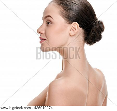 Young Woman With Perfect Healthy Skin And Hair In Bun On White Background