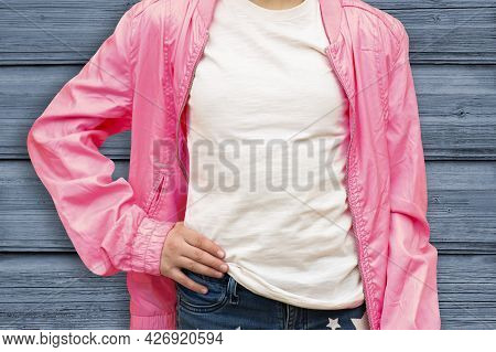 Mockup Of White Cotton T-shirt. Teenage Girl In White T-shirt And Pink Jacket Stands Against Wooden