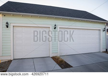 Three-car Garage Exterior With Mint Green Vinyl Wall Siding
