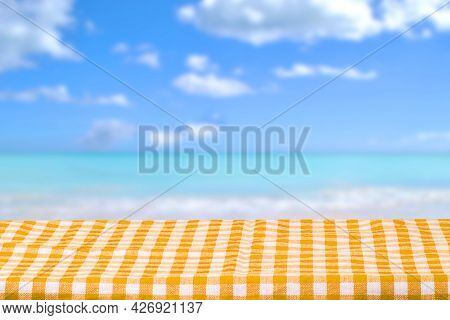 Empty Table Product. Closeup Of A Yellow Checkered Tablecloth Over Abstract Blurred Ocean Background