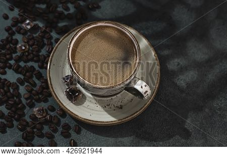Fragrant Strong Coffee And Coffee Beans On A Dark Green Concrete Background. The Concept Of Hot Drin