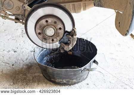 Old Brake Fluid Is Drained Into Steel Basin In Rural Car Workshop (focus On The New Brake Shoe)