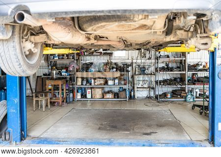 Bottom View Of Lifted Old Car In Car Workshop (focus On The Muffler In Center Of Car's Bottom)