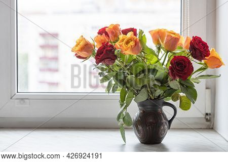 Bouquet Of Fresh Red And Yellow Rose Flowers In Ceramic Jug On Window Sill At Home With Cityscape On