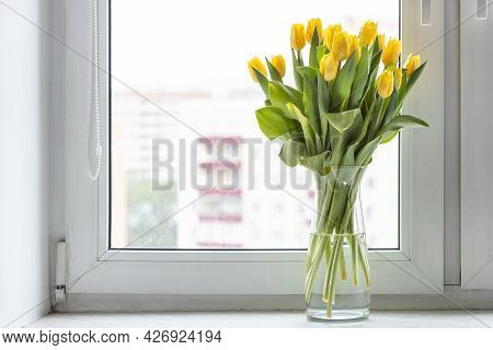 Bouquet Of Fresh Yellow Tulips In Glass Vase On Window Sill At Home With Cityscape On Background