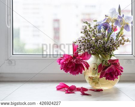 Various Flowers In Glass Vase On Window Sill At Home With Cityscape On Background