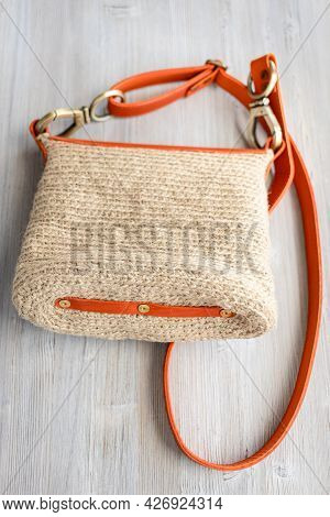 Bottom View Of Hand-knitted Casual Cross Body Bag With Orange Leather Belt On Gray Wooden Table