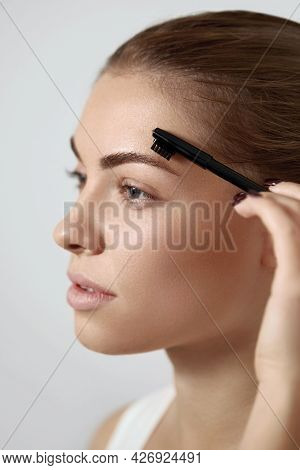 Correction And Contouring Eyebrows. Beautiful Woman Shaping Brows With Comb.  Eyebrows And Eyelashes