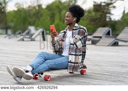 Happy Smiling African Young Girl Hold Smartphone Sitting In Urban Park On Longboard. Casual Afro Fem