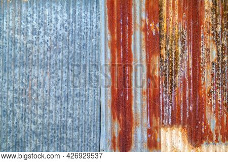 Old Galvanized Wall With Rust On It. Corrugated Zinc Siding Vintage Texture Background. Rusty Metal